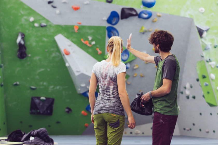 Eine Frau und ein Mann stehen vor einer Boulderwand in einer Kletterhalle und besprechen ihre Klettertaktik.
