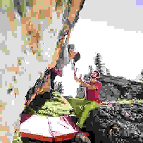 Eine Frau beim Bouldern an einer Felswand. Ein Mann gibt Hilfestellung.