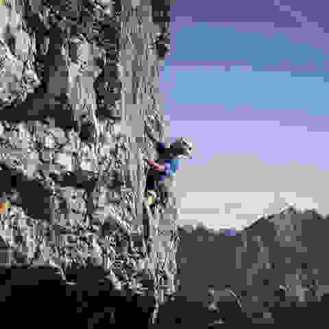 Ein Mann bouldert ungesichert an einer glatten Felswand.