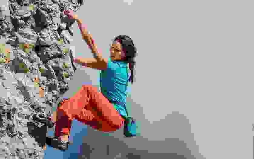 Eine Boulderin klettert an einem Sandsteingebirge. Um die Hüfte trägt sie einen schwarzen Chalkbag.