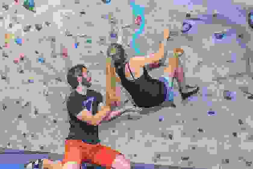 Eine Frau bouldert in der Kletterhalle. Ein Mann gibt ihr Unterstützung bei einer Übung