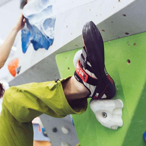 Ein Boulderschuh in der Nahaufnahme, während der Boulderer klettert.
