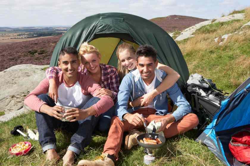 2 Jungs und 2 Mädchen sitzen vor ihrem grünen Zelt und machen sich etwas zu essen.