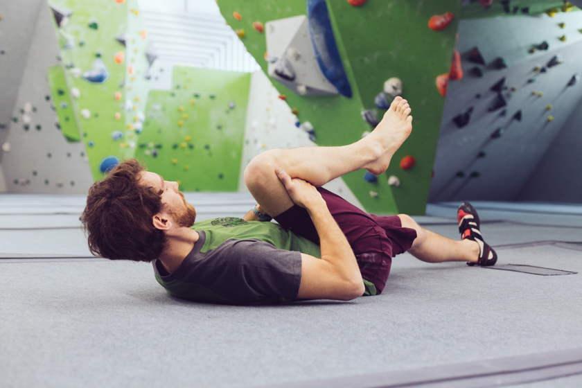 Ein Mann liegt in einer Kletterhalle zum Dehnen auf dem Boden und hat ein Bein angewinkelt und mit beiden Händen umfasst.