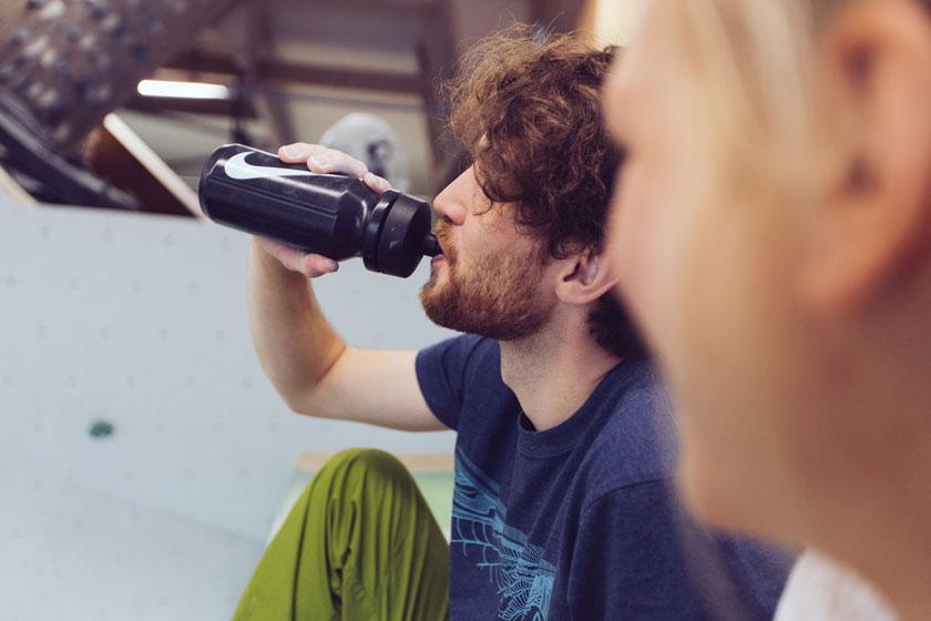 Ein Boulderer sitzt in der Boulderhalle auf dem Fussboden und trinkt aus einer schwarzen Trinkflasche.