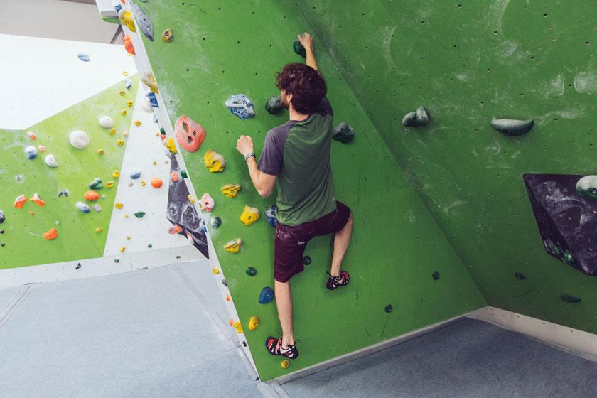 Ein Mann klettert in einer Boulderhalle und demonstriert, wie die Dreipunkt Regel auszuführen ist.