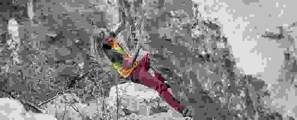 Ein langhaariger Kletterer an einer steilen Felswand.