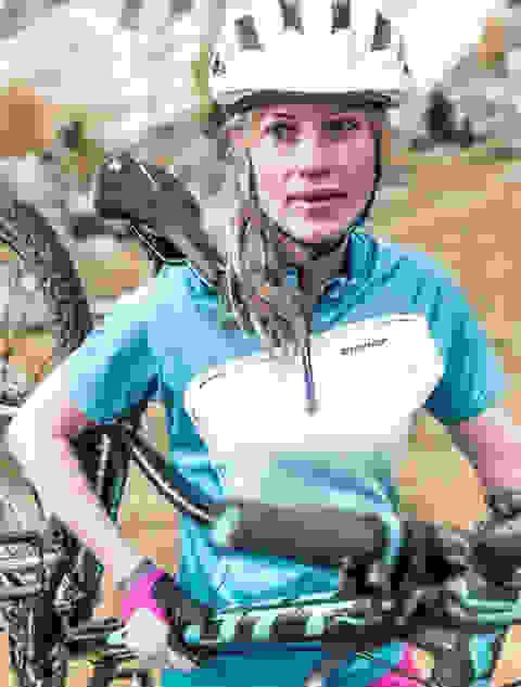Eine Frau trägt ihr Mountainbike. Sie trägt einen weißen Fahrradhelm von Scott.