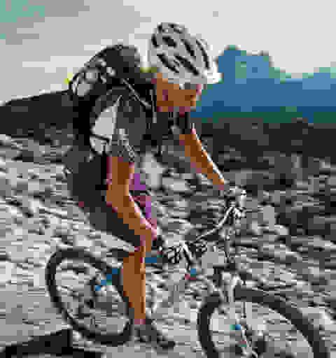 Eine Frau fährt mit einem Fahrradrucksack auf dem Rücken auf ihrem Mountainbike einen steinigen Gebirgspfad entlang.