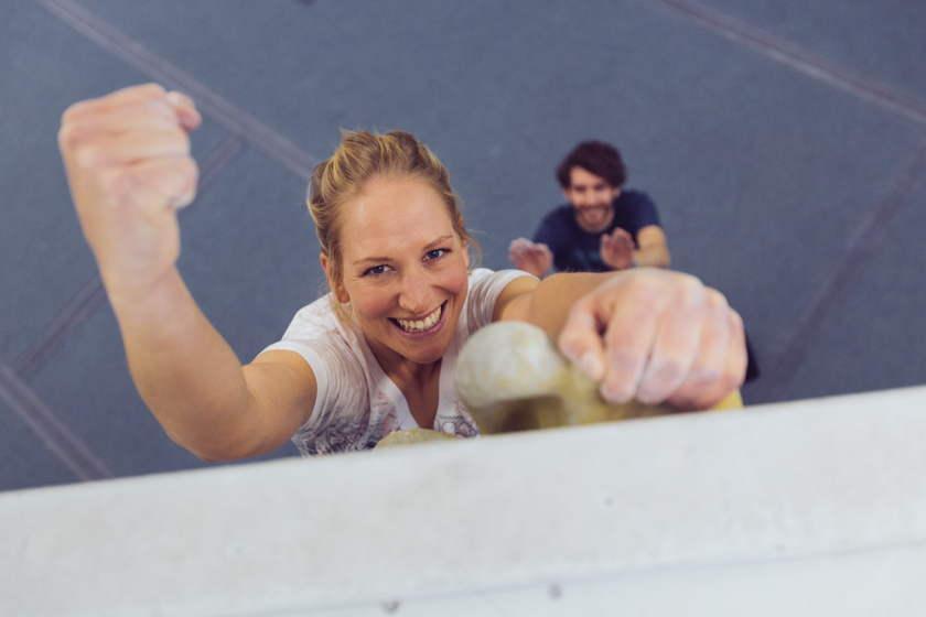 Eine Frau jubelt mit erhobener Faust hängend am letzten Boulderspot.