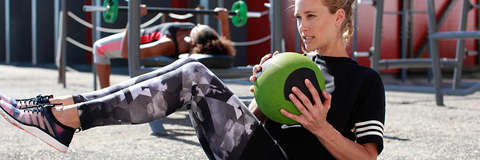 Eine Frau traininert Crunches mit einem Ball.