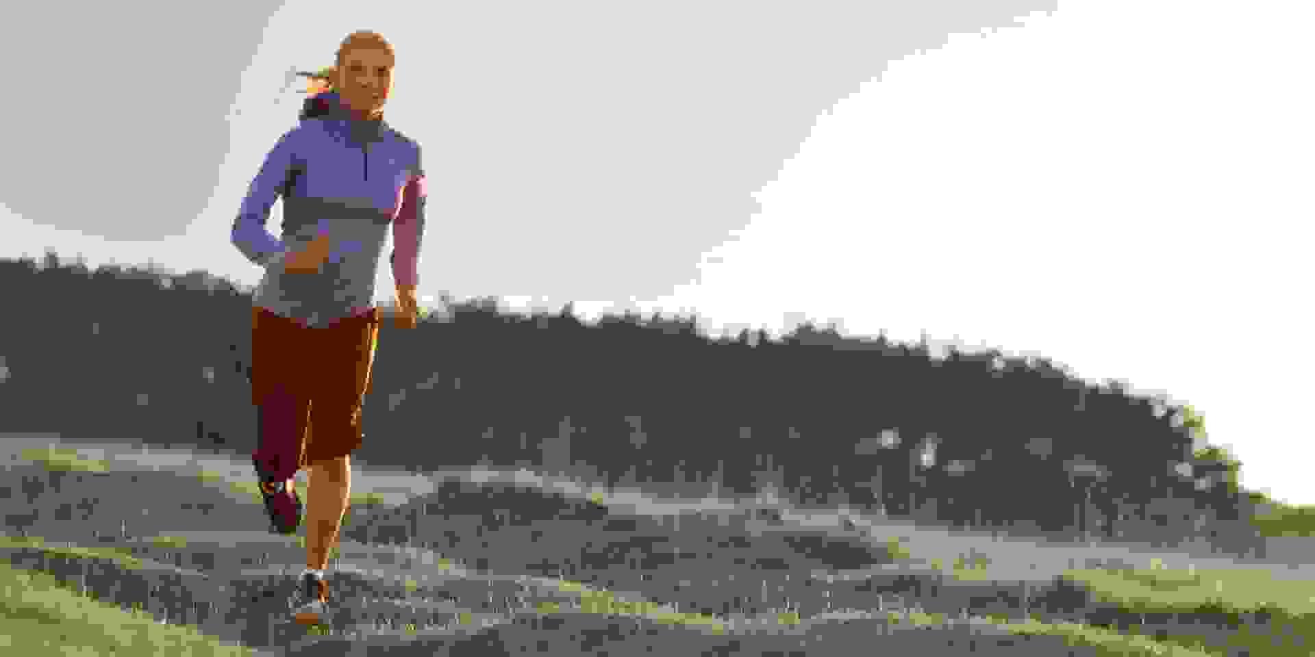 Eine Frau läuft eine hügelige Wiese entlang.