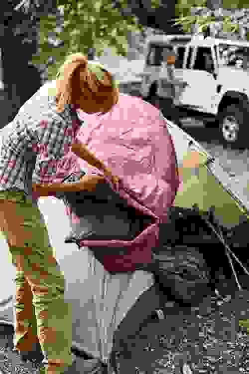 Eine Frau schüttelt einen Schlafsack aus.