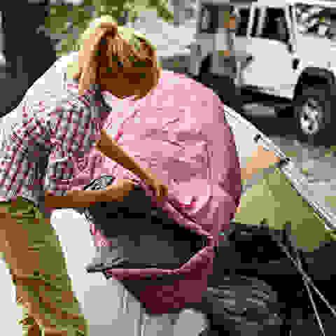Eine Frau steht vor einem Zelt und packt ihre Sachen während im Hintergrund ein SUV steht.