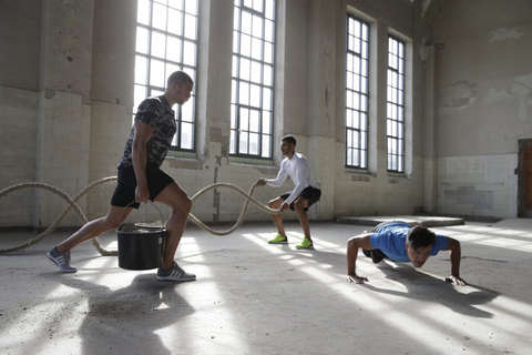 3 Männer beim Functional Training in einer Lagerhalle mit staubigem Fußboden.