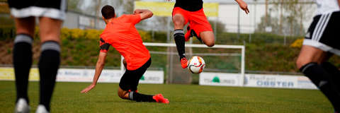 Eine Szene aus einem Fussballspiel. 2 Männer kämpfen um den Ball.