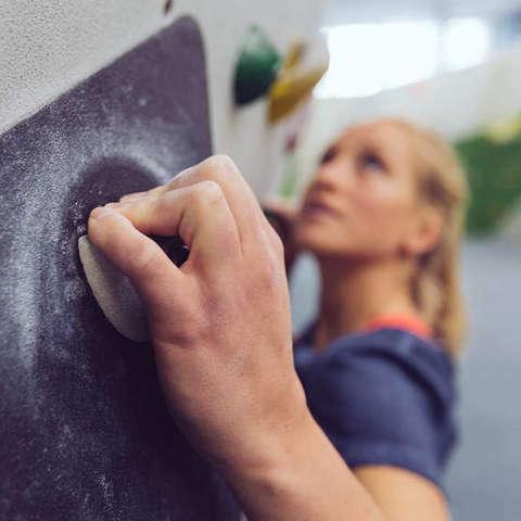 Eine Frau klettern in einer Boulderhalle.