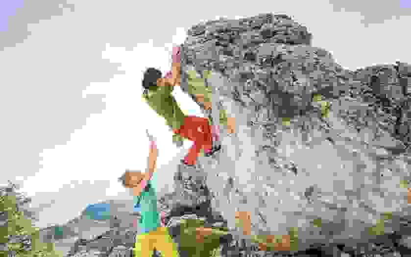 Spotten am Fels. Eine Frau sichert einen Kletterer von hinten ab.