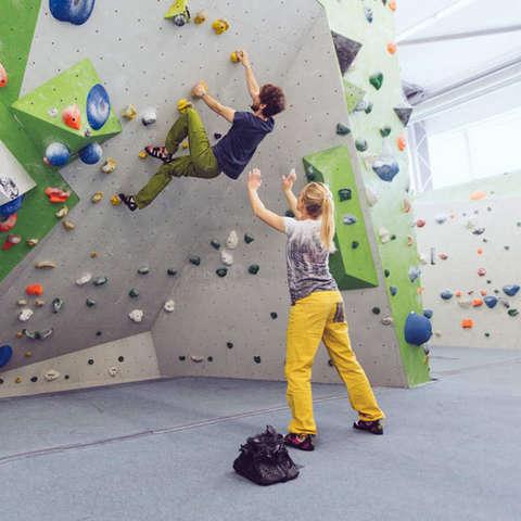 Ein Mann hängt an einer Boulderwand. Eine Frau steht mich gestreckten Armen hinter ihm, um ihn zu sichern.
