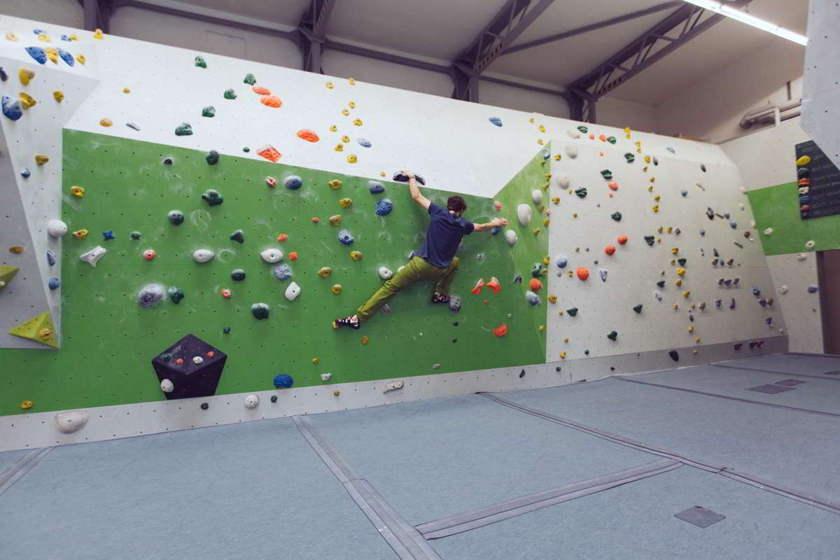 Ein Boulderer klettert waagerecht in Traversen in einer Boulderhalle an der Wand entlang.