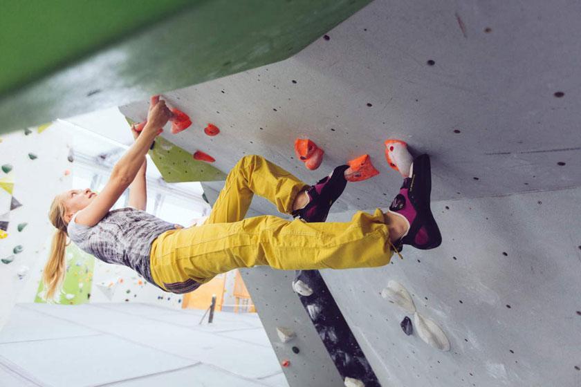 Eine Frau demonstriert in einer Kletterhalt die Technik Überhang klettern.