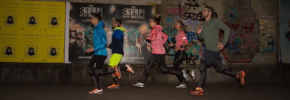 Eine Gruppe von Joggern läuft nachts eine Straße entlang.