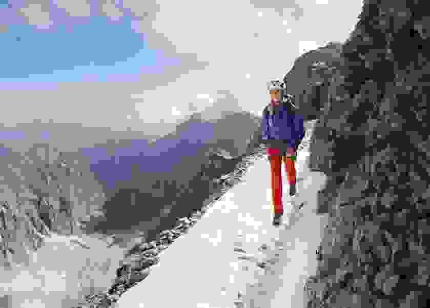 Eine Frau geht einen verschneiten Bergweg entlang.