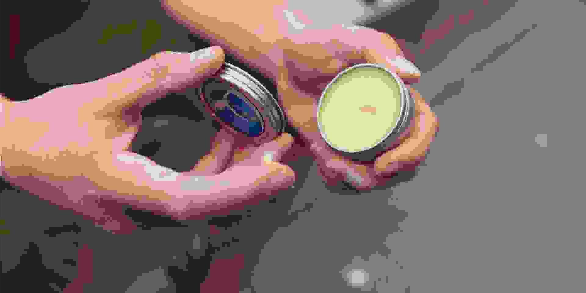 Zwei Hände, die jeweils einen Teil einer Cremedose halten.