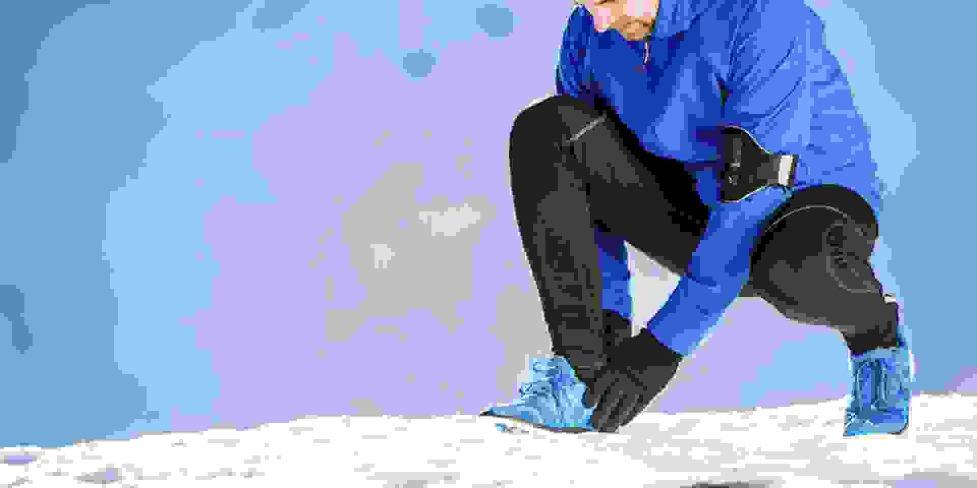 Ein Mann kniet im Schnee und bindet sich die Schuhe.