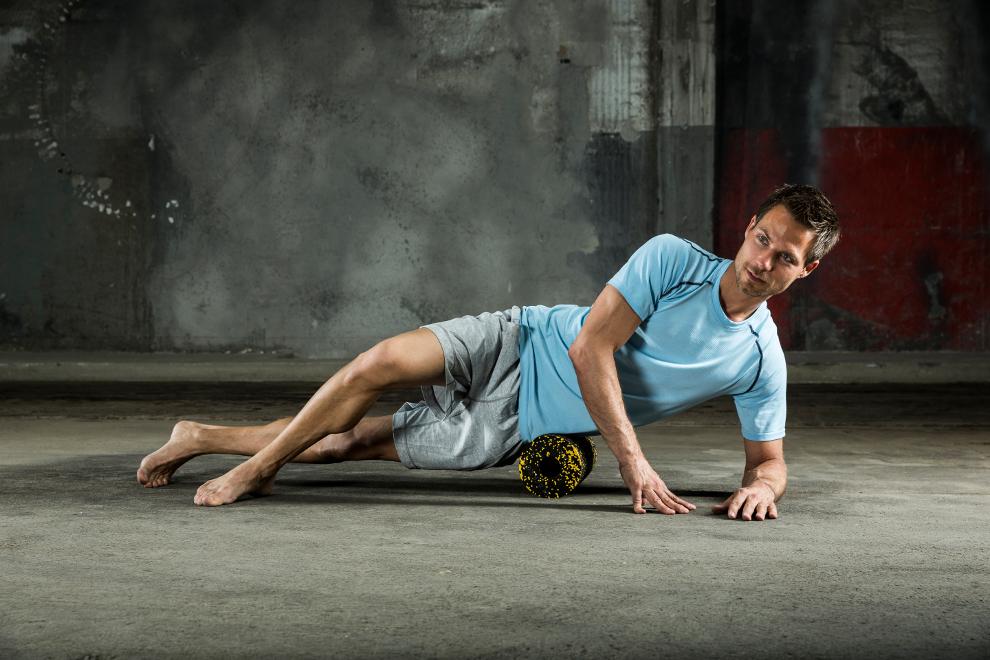 Ein Mann trainiert mit einer Blackroll seine Hüftmuskulatur.