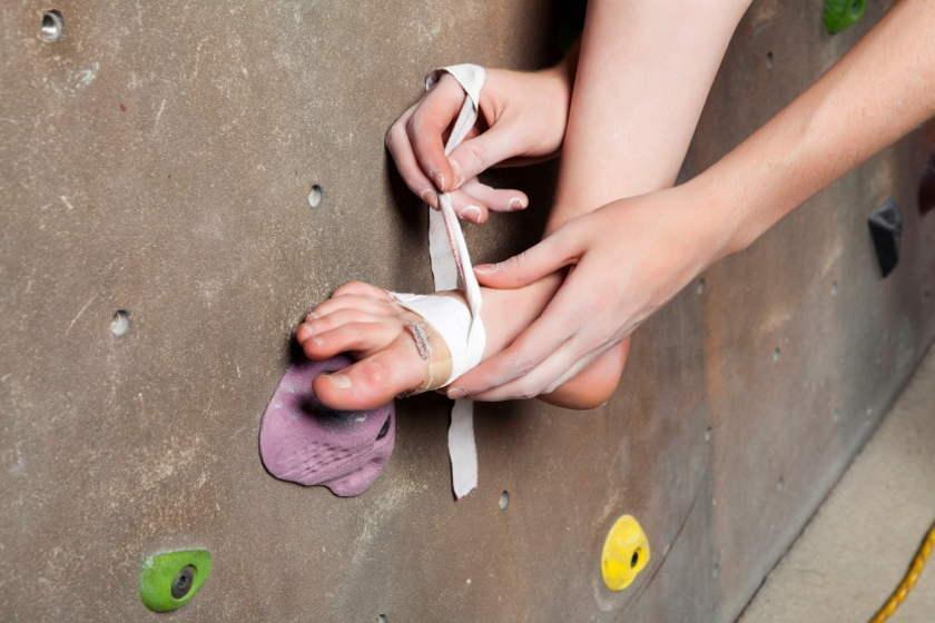 Eine Frau bandagiert ihren verletzten Fuß.