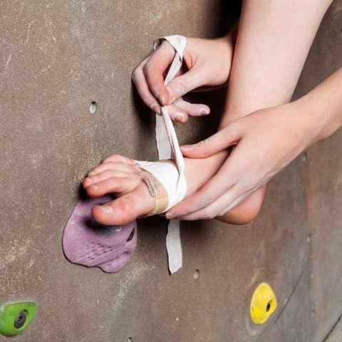 Eine Frau bandagiert ihren verletzten Fuß nach einer Boulder-Verletzung.
