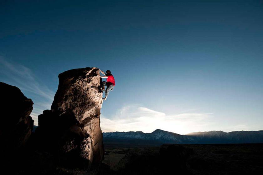 Ein Mann klettert an einem hohen Felsen ohne Sicherung hinauf.