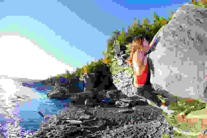 Eine Frau klettert an einem niedrigen Felsen entlang.