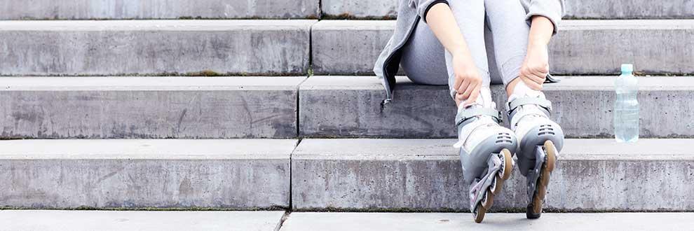 Man sieht eine Frau auf einer Steintreppe sitzen. An den Füßen trägt sie graue Inline Skates.