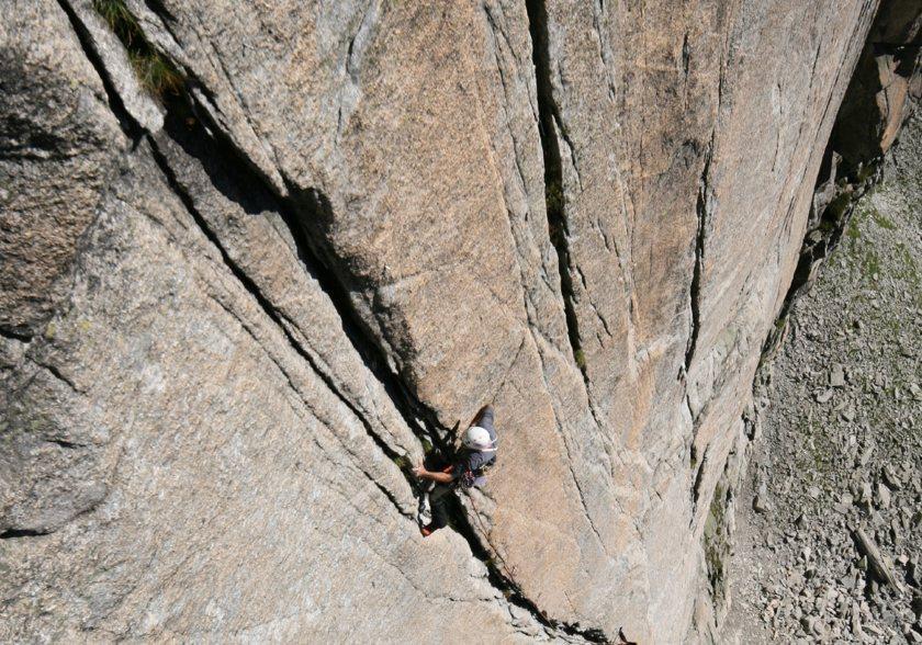 Ein Mann klettert an einer hohen und glatten Felswand an einem schmalen Spalt hinauf. Diese Technik nennt man Rissklettern.