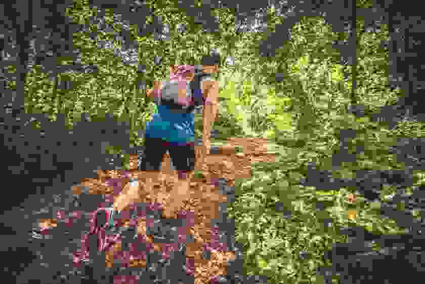 Ein Mann in schwarzer kurzer Hose und blauem Trainingsshirt läuft beim Trailrunning einen Waldweg hinauf.