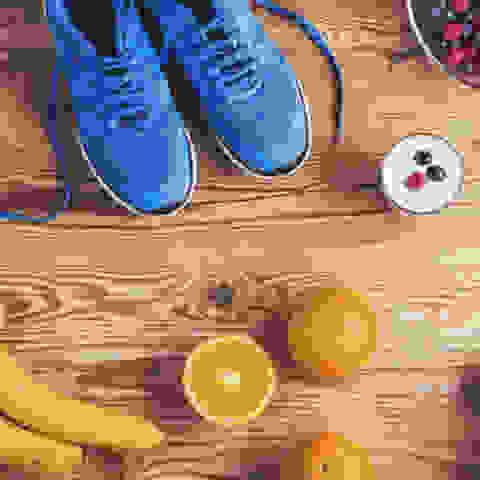 Ein Paar Laufschuhe umringt von frischem Obst und Gemüse auf einem Holztisch.