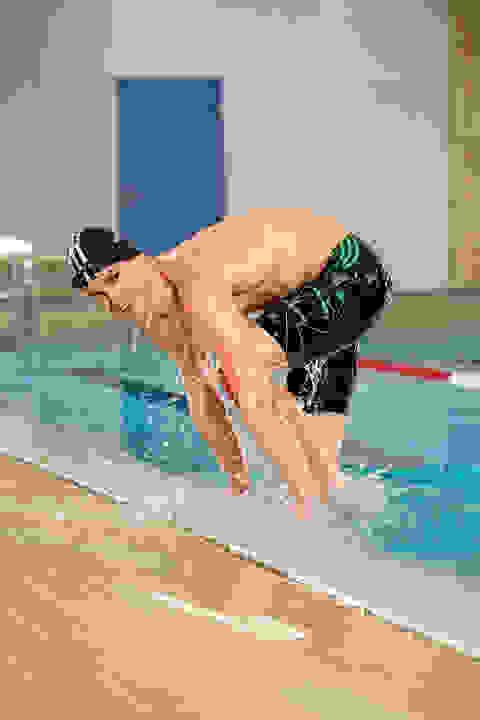 Ein Mann steigt aus einem Schwimmbecken. Er trägt eine Jammer Badehose.