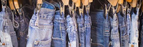 Diverse Jeanshosen für Damen auf Kleiderbügeln nebeneinander aufgehängt.