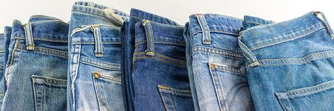 Diverse Jeanshosen für Herren nebeneinander gelegt.
