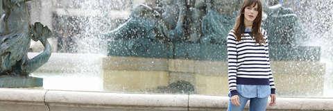 Eine dunkelhaarige Frau steht in Blue Jeans und gestreiftem Pullover vor einem Springbrunnen.