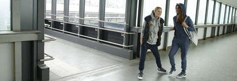 2 Frauen stehen in einem Gebäude und tragen beide einen Kapuzenpullover in Kombination mit einer Jogginghose.