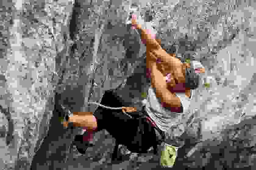 Eine Frau klettert frei an einer Felswand entlang.