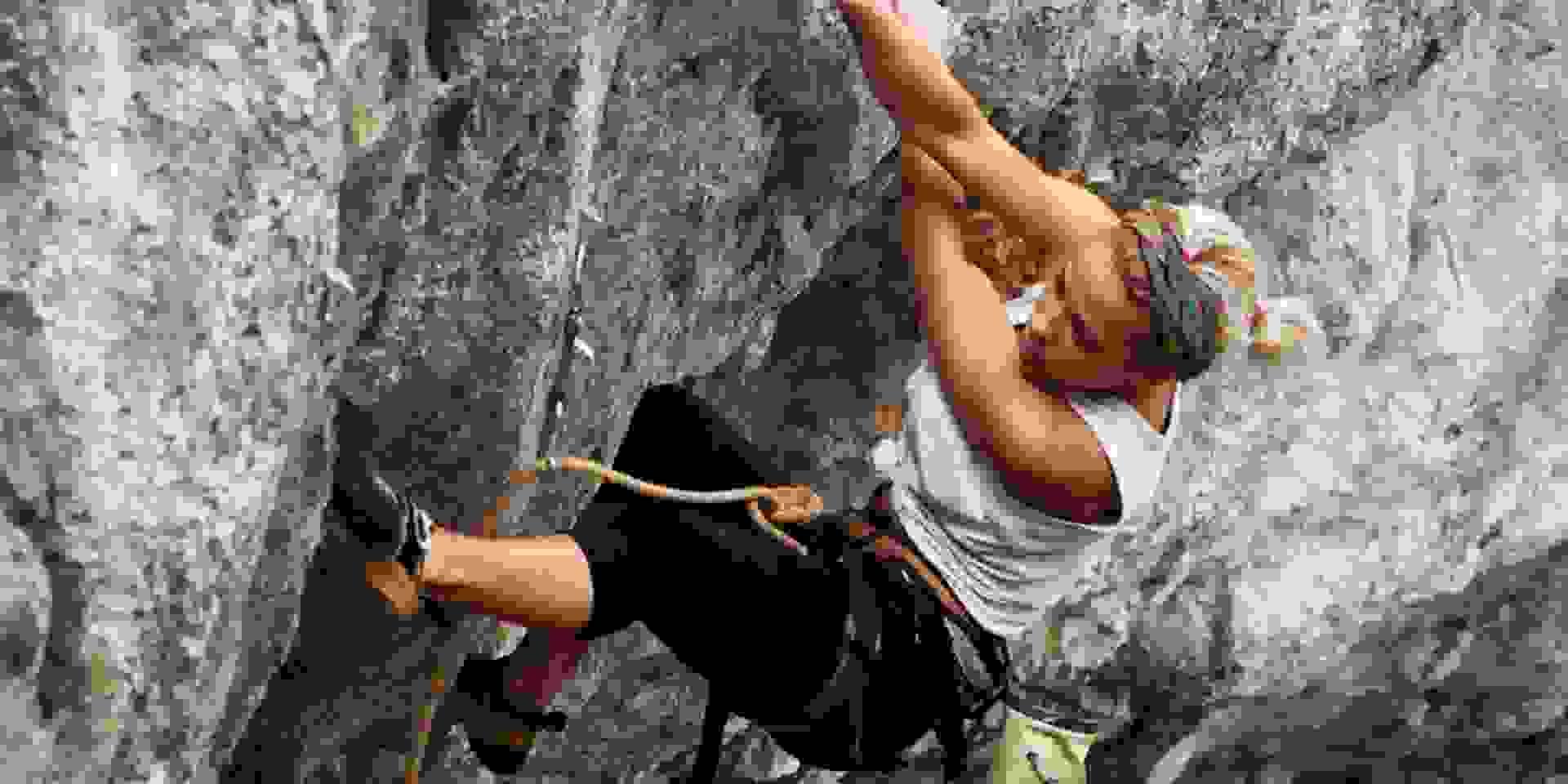 Eine Junge Frau klettert eine Route am Felsen in der freien Natur