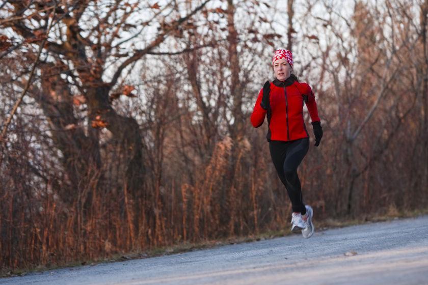 Eine Trailrunnerin läuft im Herbst eine Straße entlang.