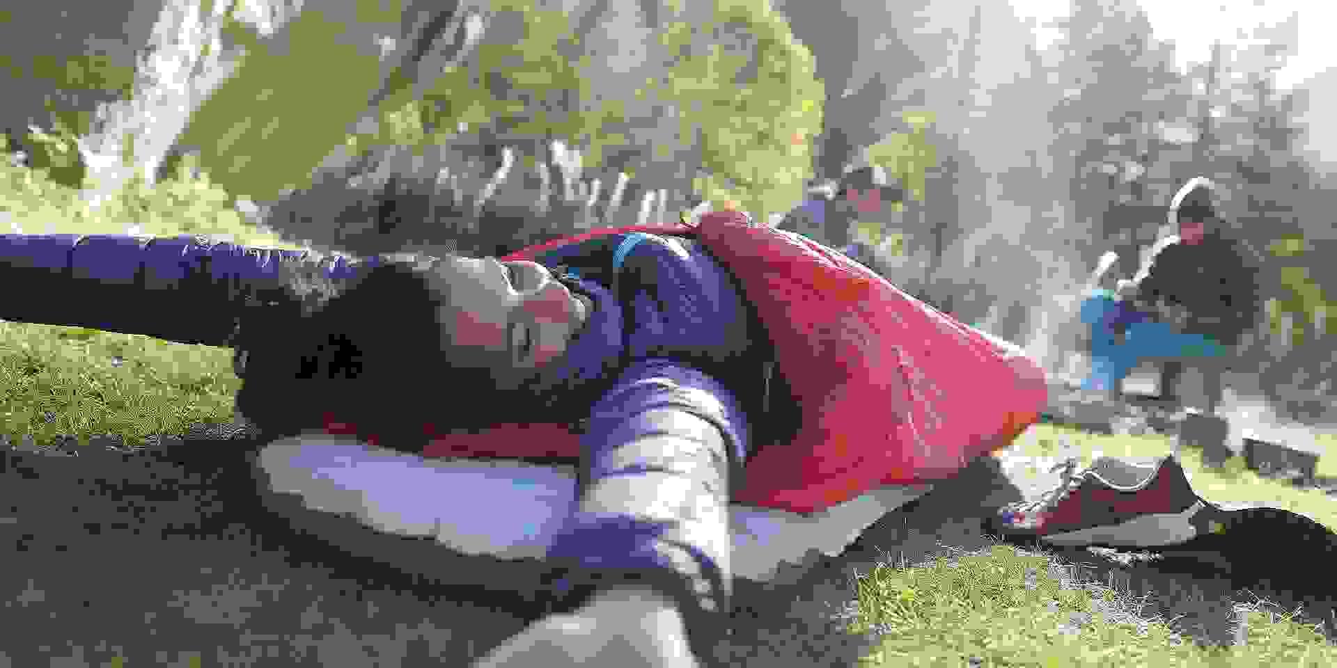 Eine Frau wacht auf nachdem sie mit Schlafsack im Freien übernachtet hat