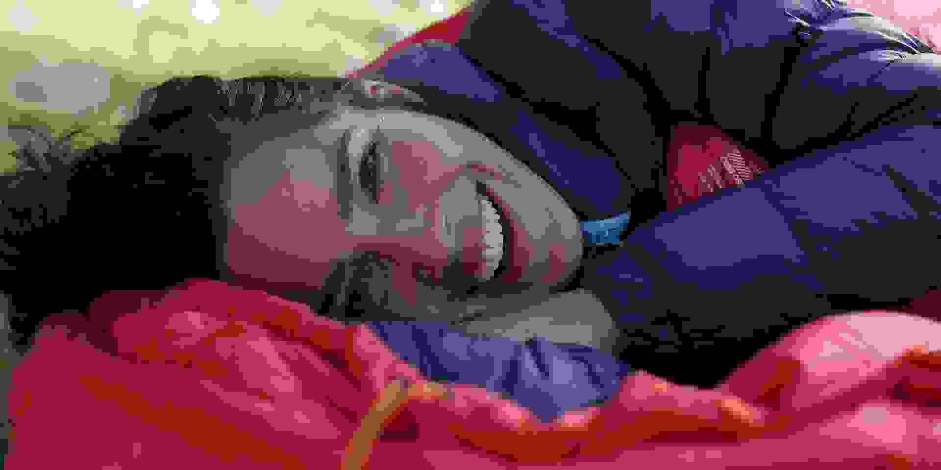 Eine Frau liegt im Freien in einem warmen Schlafsack