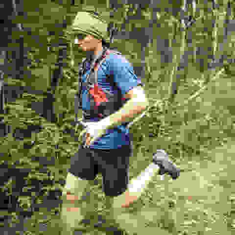 Ein Trailrunner läuft im Wald. Auf dem Kopf trägt er einen Buff.