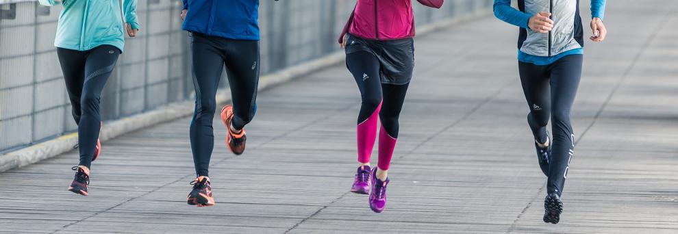 Vier Läufer laufen beim Training nebeneinander her.